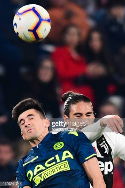Udinese's Argentine forward Ignacio Pussetto and Juventus' Uruguayan defender Martin Caceres go for a header during the Italian Serie A football...