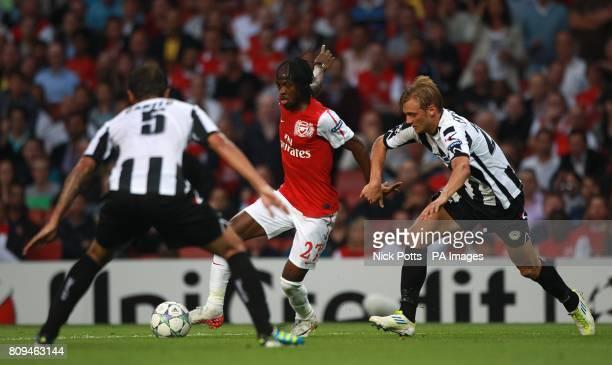 Udinese's Danilo Larangeira left0 looks on as team mate Joel Ekstrand battles for the ball with Arsenal's Yao Gervinho