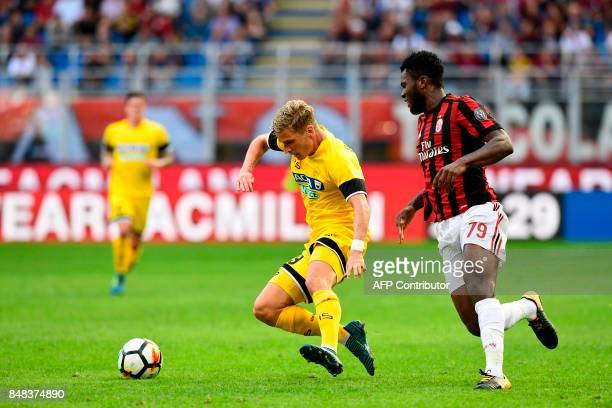 Udinese's Danish defender Jens Stryger Larsen and AC Milan's Ivoirian midfielder Franck Kessie run for the ball during the Italian Serie A football...