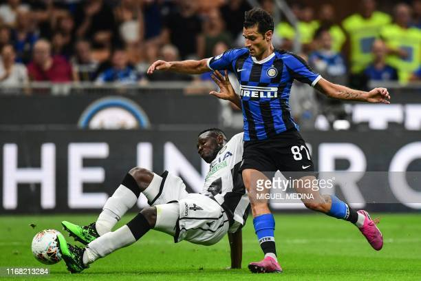 Udinese's Ghanaian defender Nicholas Opoku holds off Inter Milan's Italian forward Antonio Candreva during the Italian Serie A football match Inter...