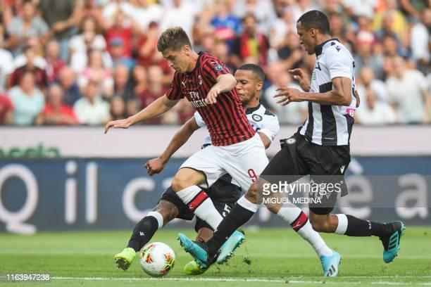 Udinese's Nigerian defender William TroostEkong and Udinese's Brazilian defender Rodrigo Becao tackles AC Milan's Polish forward Krzysztof Piatek...