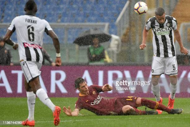 Udinese's Nigerian defender William TroostEkong heads the ball next to AS Roma Czech forward Patrik Schick during the Italian Serie A football match...
