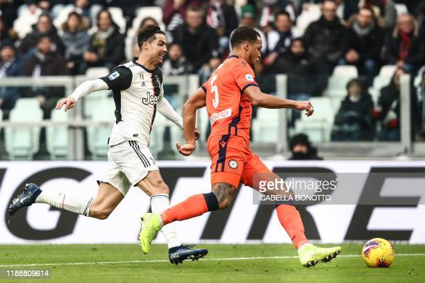 Udinese's Nigerian defender William TroostEkong outruns Juventus' Portuguese forward Cristiano Ronaldo during the Italian Serie A football match...
