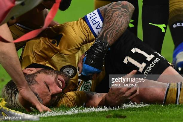 Udinese's Swiss midfielder Valon Behrami lies in pain on the pitch after a shock during the Italian Serie A football march AC Milan vs Udinese on...