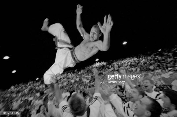 Udo Quellmalz of Germany celebrates his gold medal in the Men's 65 kg Judo competition by being thrown into the air by his team mates during the XXVI...