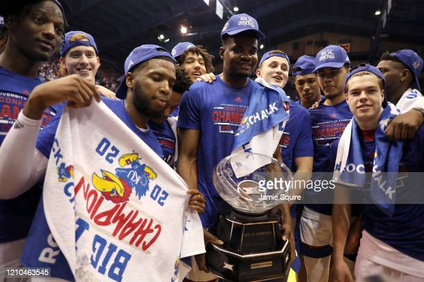 Udoka Azubuike of the Kansas Jayhawks holds the Big 12 Championship Trophy alongside teammates after defeating the TCU Horned Frogs to win the game...
