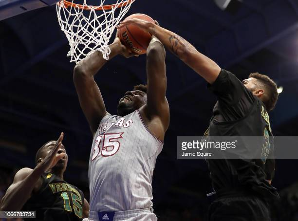 Udoka Azubuike of the Kansas Jayhawks shoots as Ra Kpedi and Anthony Lamb of the Vermont Catamounts defend during the game at Allen Fieldhouse on...