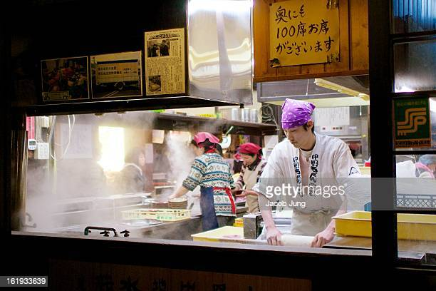 CONTENT] Udon ie wheatflour noodles chefs at work in a small restaurant with large windows in the town of Kotohira an area famous for the noodles...