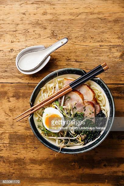 Udon noodle with boiled pork, wheat germ and egg on wooden background