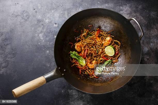 Udon noodles stir-fried with Tiger shrimps and vegetable in wok cooking pan on dark background