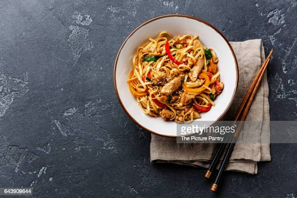udon stir-fry noodles with chicken meat and sesame in bowl on dark stone background copy space - sesame stock pictures, royalty-free photos & images