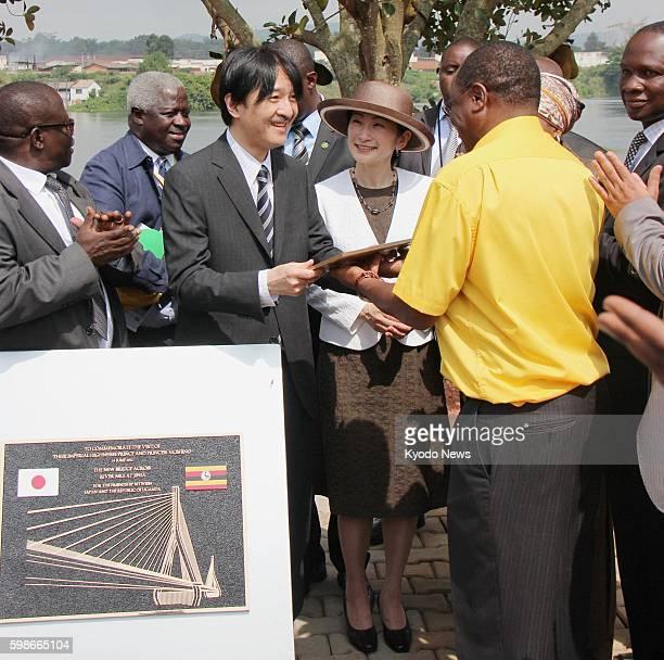 KAMPALA Uganda Japan's Prince Akishino the second son of Emperor Akihito with his wife Princess Kiko receives a memorial plate as they attend a...