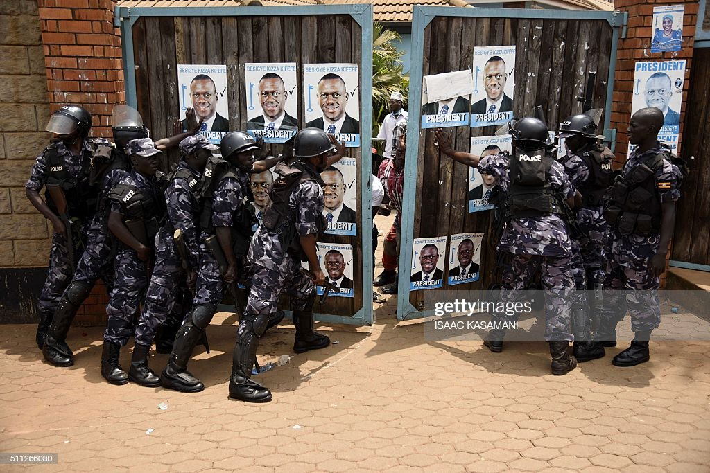 TOPSHOT - Uganda police block the gates of the opposition Forum for Democratic Change (FDC) in Kampala on February 19, 2016, during events surrounding the arrest of opposition candidate Kizza Besigye. Uganda's top presidential challenger Kizza Besigye was arrested for a third time in a week, as a chaotic election stretched into a second day. 'Kizza Besigye has been arrested from our HQ and taken to (an) unknown location,' his Forum for Democratic Change (FDC) party said. / AFP / Isaac Kasamani