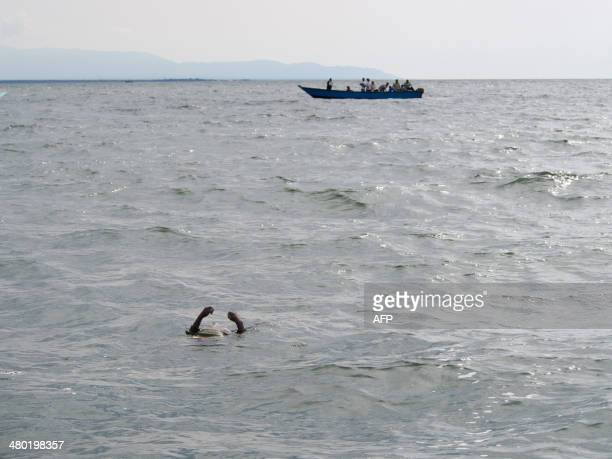 Uganda Police divers and local fishermen sail past the body of a Congolese refugee floating during their search for victims of a boat disaster on...