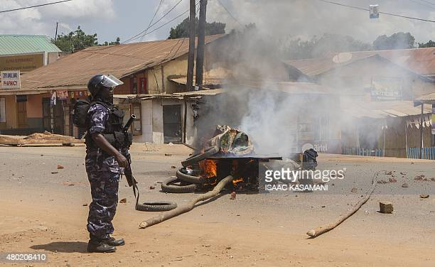 A Uganda police officer stands near a bonfire set by people demonstrating on a road in Kasangati on July 9 2015 The demonstration started after two...
