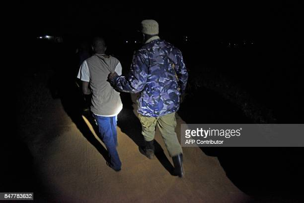 Uganda police officials and Mayumba Kumi crime preventers a community patrol team that was started by the Katabi Town Council arrest an unidentified...