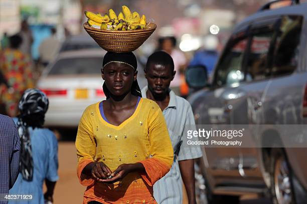 uganda: woman balances a basket of bananas on her head - kampala stock pictures, royalty-free photos & images