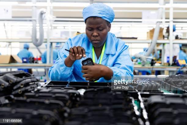 Ugandan factory workers assemble mobile phone cases on December 02 2019 in Namanve Uganda Uganda's first mobile phone electronics factory has been...