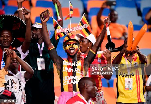 A Ugandan football fan wearing body paint and a hat showing his country's national colours and mascot as he holds a vuvuzela during the 2019 Africa...