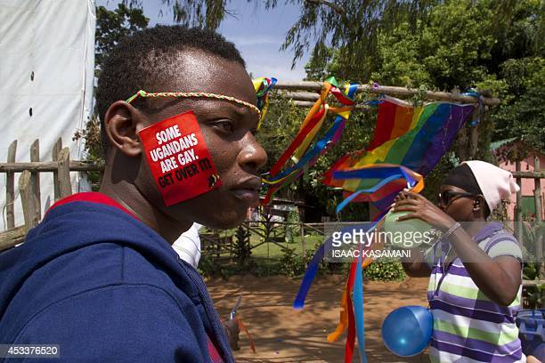 A Ugandan man with a sticker on his face takes part on August 9 2014 in the annual gay pride in Entebbe Uganda Uganda's attorney general has filed an...