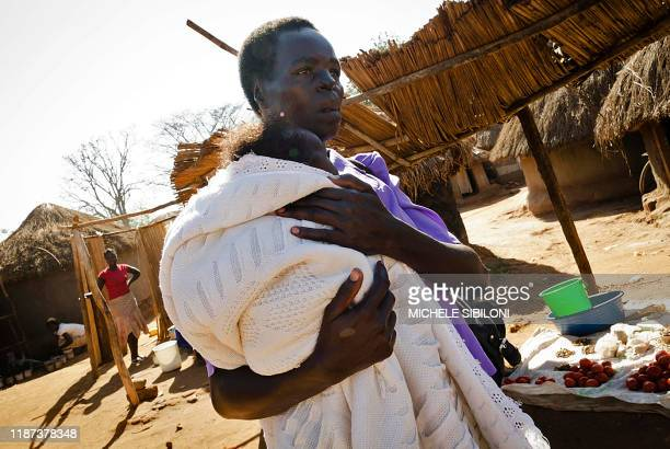 Ugandan MargaretaOtto walks on February 1, 2012 with her one-year-old child on the way to the market in the northern Ugandan city of Gulu. Otto has...