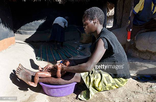 Ugandan MargaretaOtto washes on February 1, 2012 her one-year-old child in the northern Ugandan city of Gulu. Otto has five children and she bears...