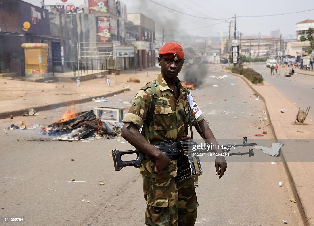A Ugandan military police officer walks past a burning barricade across a street in Kampala on February 19, 2016, during the second day of voting in presidential elections. Dozens of polling stations in Uganda were forced to open for a second day on February 19, 2016 after the late delivery of ballot boxes and voting papers prevented many from casting their ballots. / AFP / Isaac Kasamani