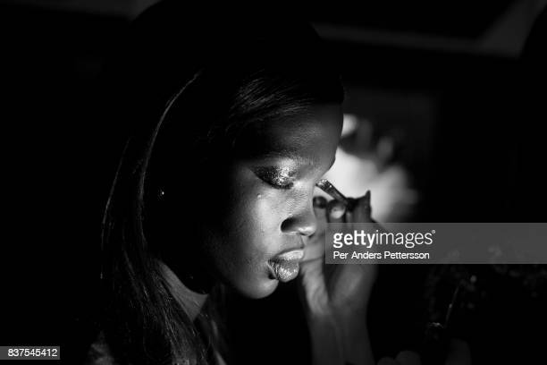 Ugandan model Aamito Lagum gets her makeup done before a show with the South African designer label Fabiani on August 19 2017 in Mall of Africa north...