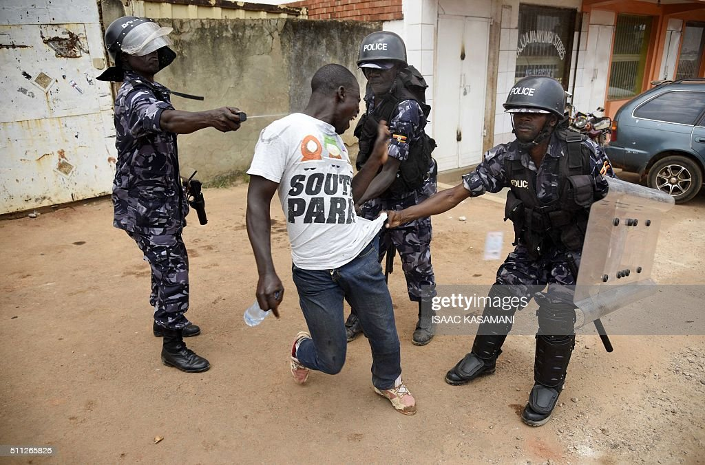 Ugandan police officer sprays tear gas onto a protestor after he was aprehended in Kampala on February 19, 2016, during the second day of voting in presidential elections. Dozens of polling stations in Uganda were forced to open for a second day on February 19, 2016 after the late delivery of ballot boxes and voting papers prevented many from casting their ballots. / AFP / Isaac Kasamani