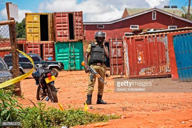 A Ugandan police officer talks on his mobile phone as police secures the cordoned off site following a joint Uganda Police Force and Army security...