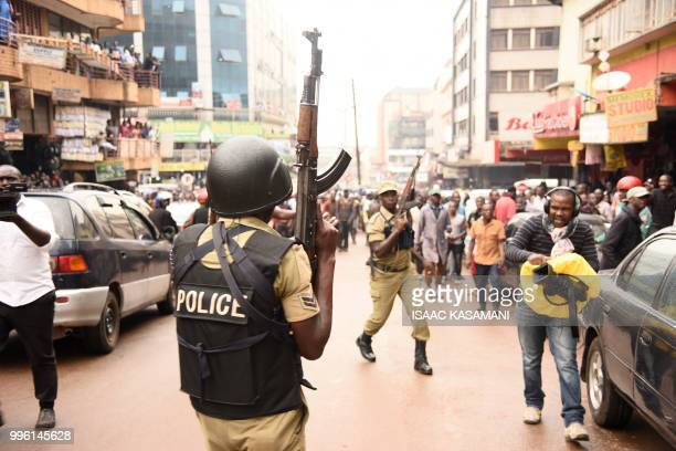 Ugandan police officers are seen lifting their AK47 riffle aloft opposite protesters during a demonstration on July 11 2018 in Kampala to protest a...