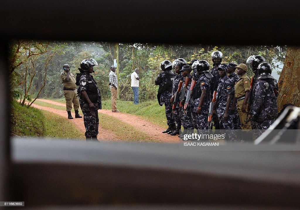 Ugandan police officers stand guard outside the house of Uganda's main opposition leader Kizza Besigye home on February 22, 2016 in Kasangati, suburb of Kampala. Uganda's main opposition leader was taken by police on February 22, 2016 to a city police station from his home where he has been under house arrest since February 19. Kizza Besigye has rejected the results of February 18 election won by veteran President Yoweri Museveni, and called on his supporters to join a protest march on February 22. / AFP / Isaac Kasamani