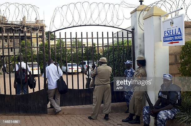 Ugandan police officers stay at the entrance of the Esella Country Hotel after police raided a gay rights workshop which was taking place in the...