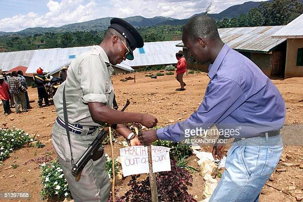 Ugandan policemen put up 21 March 2000 a sign telling people to keep out of the church grounds of the Restoration of the Ten Commandements of God...