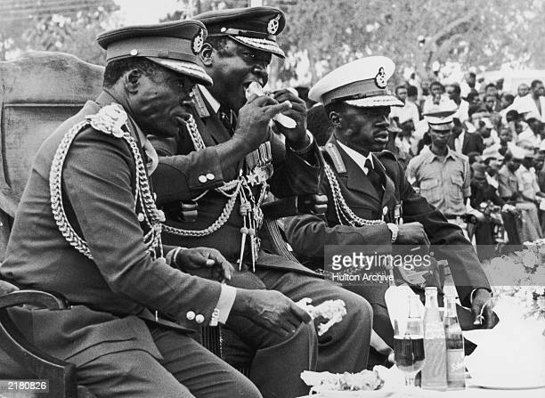 Ugandan President Idi Amin eating a roast chicken leg while watching a parade in Koboko to celebrate the seven year anniversary of his military coup...