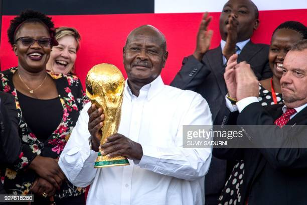 Ugandan President Yoweri Museveni holds the FIFA World Cup Trophy at the State House in Entebbe on March 5 2018 as part of the football...