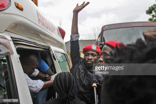 Ugandan singerturnedpolitician Robert Kyagulanyi better known as Bobi Wine reacts as he gets into an ambulance after being released on bail at The...