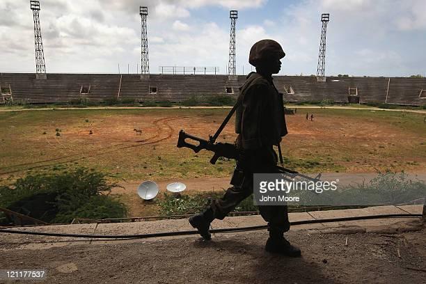 Ugandan soldier, part of the 9,000-strong African Union Mission in Somalia, walks through the Banadir soccer stadium on August 15, 2011 in Mogadishu,...