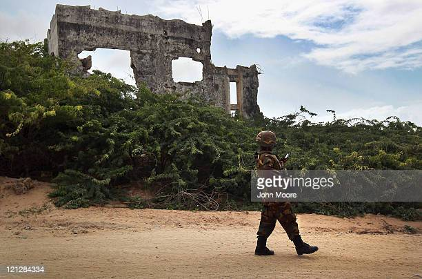 Ugandan soldier, part of the African Union Mission in Somalia , checks his smart phone while walking past war rubble on an AMISOM base on August 17,...