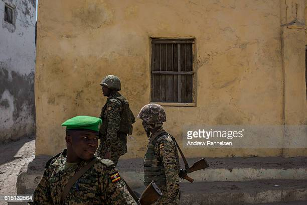 Ugandan soldiers deployed with the African Union Mission in Somalia walk through the streets of Barawe on October 11 2016 in Barawe Somalia The city...