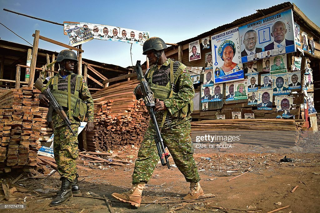 TOPSHOT - Ugandan soldiers walk past election posters in Kampala on February 19, 2016 during the presidential election vote. Voting was extended in 36 sites for a second day after delays on February 18 that Commonwealth election observers called 'inexcusable'. Some frustrated voters accused the authorities of deliberately stalling the vote. Ugandan President Yoweri Museveni is widely predicted to win a fifth term. / AFP / CARL
