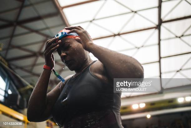 Ugandan swimmer Clare Byarugaba reacts after competing during the swimming competition at the 2018 Gay Games edition at The GeorgesVallerey swimming...
