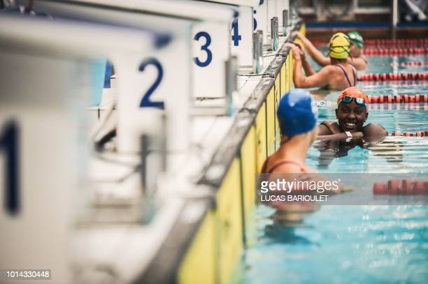 Ugandan swimmer Clare Byarugaba speaks with another athlete during the swimming competition at the 2018 Gay Games edition at The GeorgesVallerey...