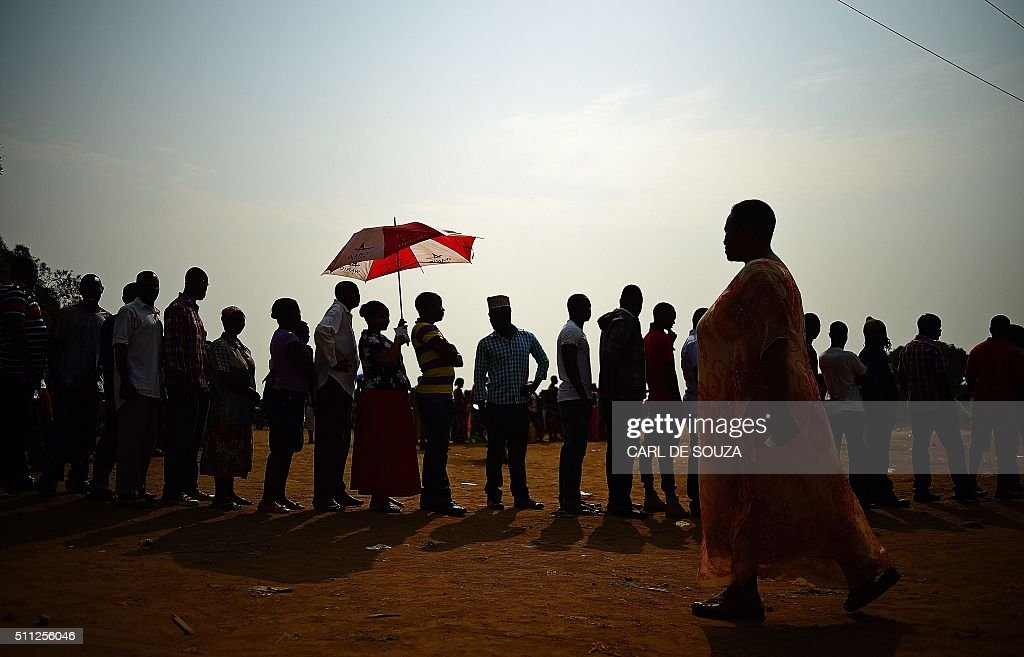 TOPSHOT - Ugandan voters who were unable to vote the first day, queue outside polling stations, in Kampala on February 19, 2016. Dozens of polling stations in Uganda were forced to open for a second day on February 19, 2016 after the late delivery of ballot boxes and voting papers prevented many from casting their ballots. President Yoweri Museveni, 71, is expected to win re-election, winning a fifth term in office and extending his 30-year rule of the east African country. In the capital Kampala, Thursday's elections were disrupted by the late arrival of polling materials, angry demonstrations by frustrated voters, police use of tear gas and the brief arrest of an opposition candidate. A total of 36 polling stations in the city and the surrounding Wakiso district were due to reopen on February 19 morning. / AFP / CARL
