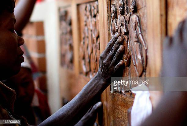 Ugandan women pray at the relief doors of the Martyrs shrine in Namugongo in Kampala on June 3 2011 during the yearly Martyrs day celebration which...