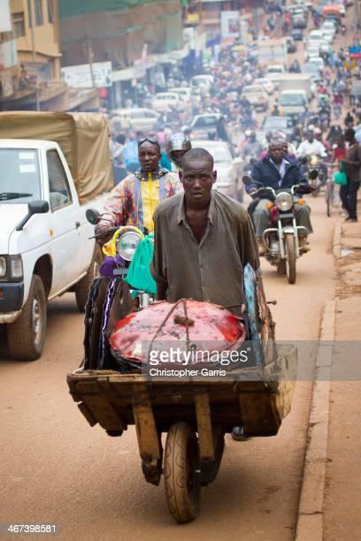 Ugandan worker transports steel drum lids in a wooden wheelbarrow on a busy exhaustfilled urban Kampala street
