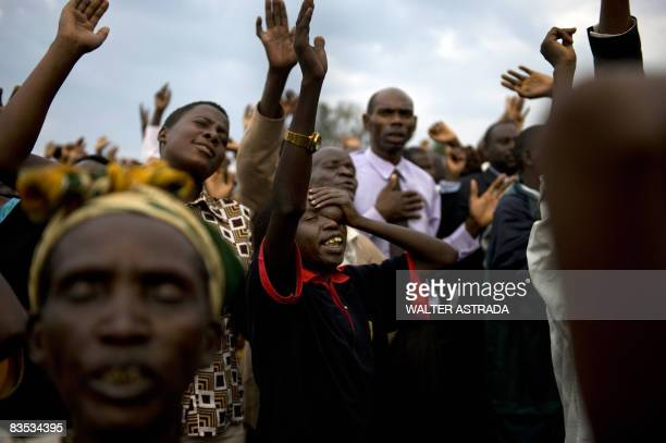 Ugandans pray as they attend a a massive preach of the Born Again Church lled by Pastor Robert Kayanja one of Uganda's wealthiest and most prominent...