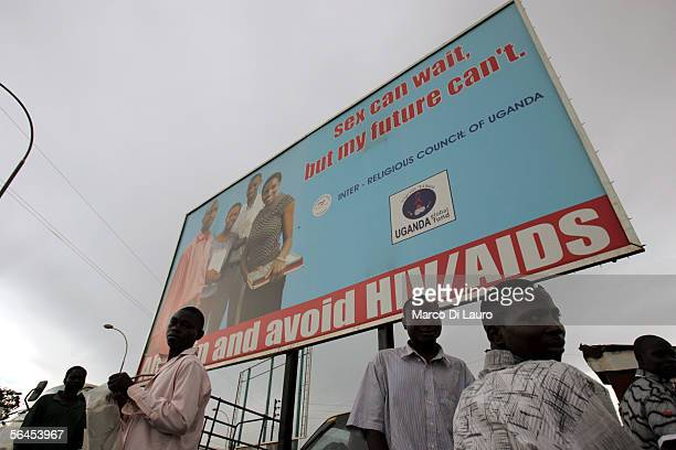 Ugandans stand next to a street advertisment promoting AIDS awarenesson December 4 2005 in Kampala Uganda The Church of Uganda has been very active...