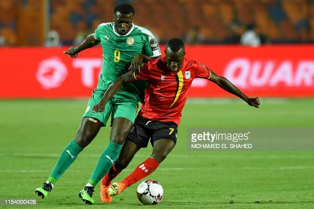 Uganda's forward Emmanuel Okwi fights for the ball against Senegal's forward M'baye Diagne during the 2019 Africa Cup of Nations Round of 16 football...