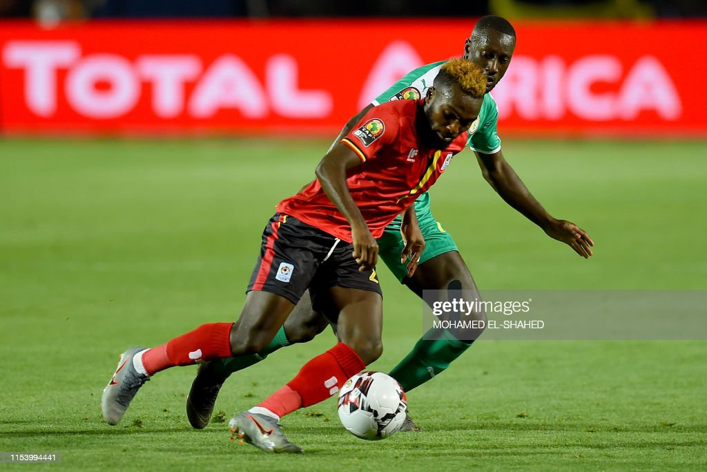 Uganda's forward Lumala Abdu fights for the ball with Senegal's